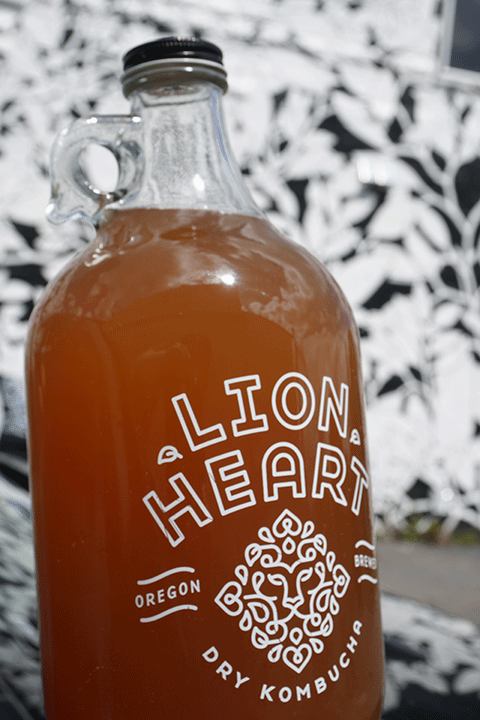 Lion Heart Kombucha in a growler from Portland, OR, with a black and white floral background.