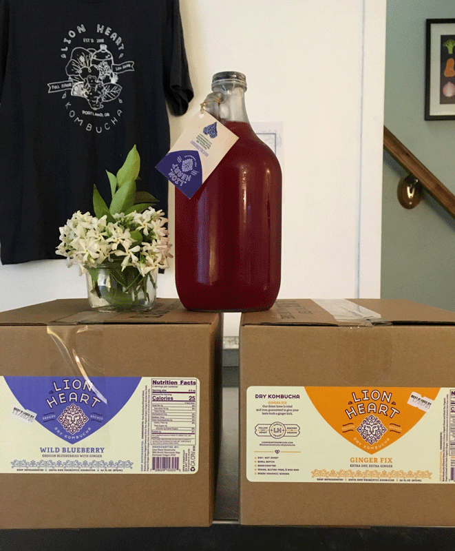 Lion Heart Kombucha in a growler with flowers on top of cases of pints and a Lion Heart Kombucha shirt in the background